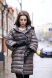 Retrato de una muchacha morena elegante joven en del gris una chaqueta abajo Fotos de archivo libres de regalías