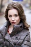 Retrato de una muchacha morena elegante joven en del gris una chaqueta abajo Foto de archivo