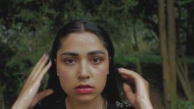Retrato de una muchacha morena hermosa con maquillaje un jet del agua vierte sexual en la cara de la muchacha desde arriba 4K v?d metrajes