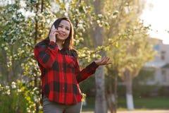 Retrato de una muchacha morena joven feliz con un smartphone en su mano, aumentado a su o?do Muchacha que habla en m?vil y la son imagen de archivo libre de regalías