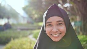 Retrato de una muchacha musulmán sonriente joven en un hijab negro almacen de video