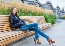 Retrato de una muchacha muy hermosa en el parque en el banco Foto de archivo