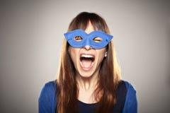 Retrato de una muchacha normal que grita con una máscara azul Fotos de archivo libres de regalías