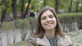 Retrato de una muchacha o de una mujer muy hermosa que ríe muy emocionalmente en un parque y miradas de la ciudad en la cámara almacen de metraje de vídeo