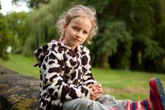 Retrato de una muchacha de ojos azules rizada hermosa que se sienta en un fondo de árboles verdes Vacaciones en el pueblo fotografía de archivo