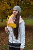 Retrato de una muchacha oscuro-cabelluda entre las hojas de otoño Foto de archivo libre de regalías