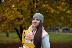 Retrato de una muchacha oscuro-cabelluda entre las hojas de otoño Imagen de archivo