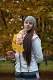 Retrato de una muchacha oscuro-cabelluda entre las hojas de otoño Foto de archivo