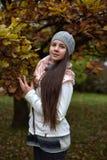 Retrato de una muchacha oscuro-cabelluda entre las hojas de otoño Fotografía de archivo libre de regalías