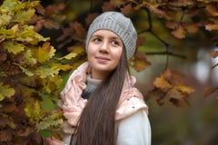 Retrato de una muchacha oscuro-cabelluda entre las hojas de otoño Imagenes de archivo