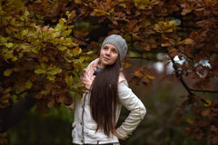 Retrato de una muchacha oscuro-cabelluda entre las hojas de otoño Imagen de archivo libre de regalías