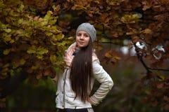 Retrato de una muchacha oscuro-cabelluda entre las hojas de otoño Fotografía de archivo