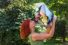Retrato de una muchacha pelirroja encantadora que se coloca en el parque encendido imagen de archivo