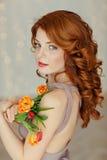 Retrato de una muchacha pelirroja hermosa con los ojos azules que sostienen a Imagen de archivo