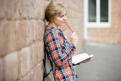 Retrato de una muchacha pensativa del estudiante contra la pared de ladrillo, soñando Fotos de archivo