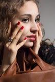 Retrato de una muchacha pensativa hermosa con las manos en cara Imagen de archivo libre de regalías