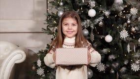 Retrato de una muchacha pequeña y feliz que está sosteniendo una caja con un regalo de Navidad y la está dando metrajes