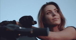 Retrato de una muchacha que admira la puesta del sol que se sienta en una opinión inferior de la motocicleta almacen de metraje de vídeo
