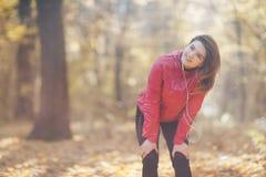 Retrato de una muchacha que entrena y escucha la música en el parque del otoño de la mañana Foto de archivo libre de regalías