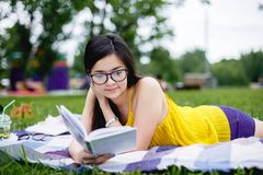 Retrato de una muchacha que lee un libro en el parque Imágenes de archivo libres de regalías