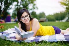 Retrato de una muchacha que lee un libro en el parque Imagen de archivo libre de regalías