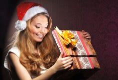 Retrato de una muchacha que lleva a cabo un regalo de Navidad Fotos de archivo libres de regalías