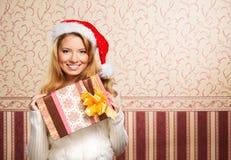 Retrato de una muchacha que lleva a cabo un regalo de Navidad Imágenes de archivo libres de regalías