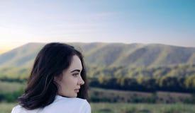 Retrato de una muchacha que mira lejos en el fondo de las montañas Imagen de archivo