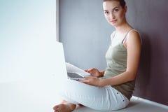 Retrato de una muchacha que se sienta en piso y que usa el ordenador portátil Fotografía de archivo