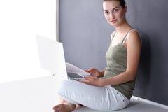 Retrato de una muchacha que se sienta en piso y que usa el ordenador portátil Imágenes de archivo libres de regalías