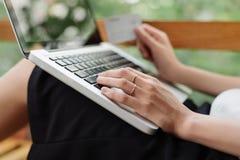 Retrato de una muchacha que sostiene la tarjeta de cr?dito y que usa el ordenador port?til Compras en l?nea imagenes de archivo