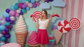 Retrato de una muchacha que sostiene los zapatos rosados en sus manos en estudio con los dulces enormes almacen de video