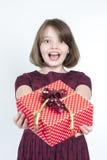 Retrato de una muchacha que sostiene un regalo al espectador Fotografía de archivo libre de regalías