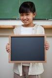 Retrato de una muchacha que sostiene una pizarra de la escuela Imagen de archivo