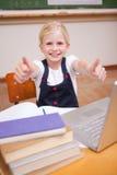 Retrato de una muchacha que usa un cuaderno con los pulgares para arriba Imagen de archivo libre de regalías