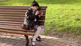 Retrato de una muchacha que usa un teléfono móvil en el parque mientras que se sienta en un banco en un día soleado almacen de video