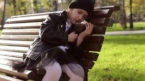 Retrato de una muchacha que usa un teléfono móvil en el parque mientras que se sienta en un banco en un día soleado almacen de metraje de vídeo