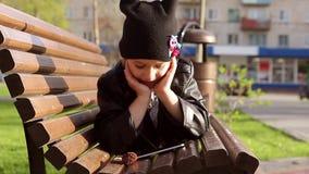 Retrato de una muchacha que usa un teléfono móvil en el parque mientras que se sienta en un banco en un día soleado metrajes