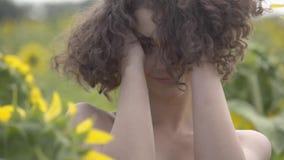Retrato de una muchacha rizada hermosa que presenta y que mira la cámara que toca su pelo que se coloca en el campo del girasol metrajes