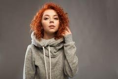 Retrato de una muchacha rizado-cabelluda joven hermosa con el pelo rojo ardiente que mira la cámara en un fondo gris Fotografía de archivo