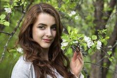 Retrato de una muchacha rodeada por los árboles florecientes del blanco Imágenes de archivo libres de regalías