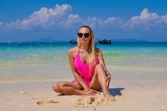 Retrato de una muchacha rubia joven que se sienta en la orilla del océano Fotografía de archivo