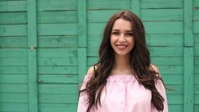 Retrato de una muchacha sonriente contra una pared verde almacen de metraje de vídeo