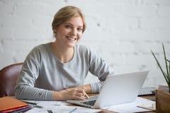 Retrato de una muchacha sonriente del estudiante en el escritorio con el ordenador portátil Imagen de archivo