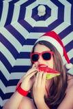 Retrato de una muchacha sonriente divertida en el sombrero de Santa Claus Fotos de archivo libres de regalías
