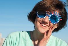 Retrato de una muchacha sonriente en gafas de sol divertidas Fotografía de archivo
