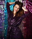 Retrato de una muchacha sonriente feliz en un vestido atractivo elegante con las lentejuelas en un partido de la moda imagen de archivo
