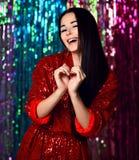 Retrato de una muchacha sonriente feliz en un vestido rojo atractivo elegante con los soplos en un partido de la moda imágenes de archivo libres de regalías