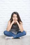 Retrato de una muchacha sonriente feliz hermosa que se sienta en el piso Imagen de archivo libre de regalías