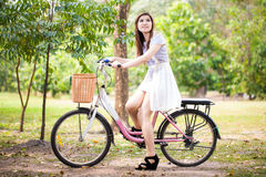 Retrato de una muchacha sonriente feliz que monta una bicicleta en el parque Fotos de archivo